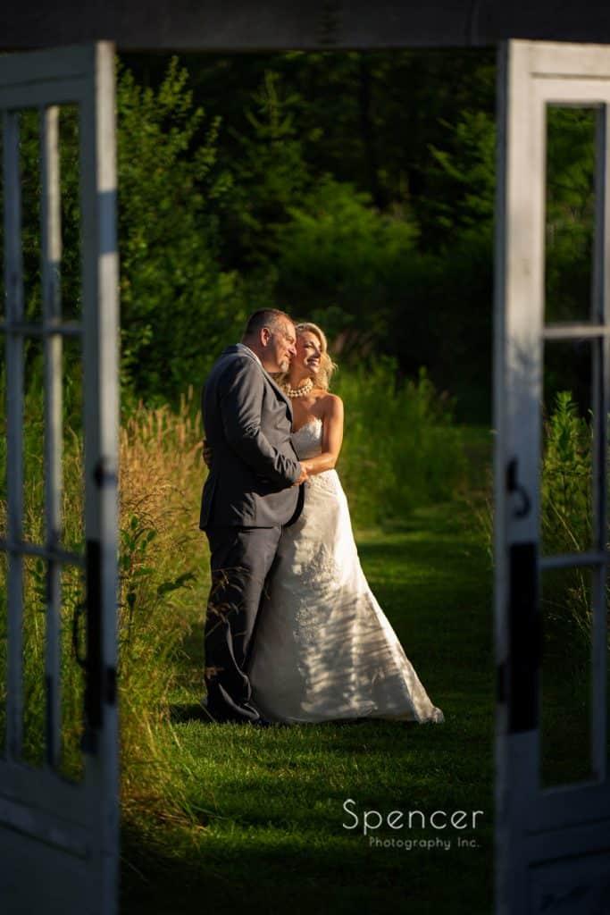 wedding picture of bride and groom shot thru barn doors at Thorncreek