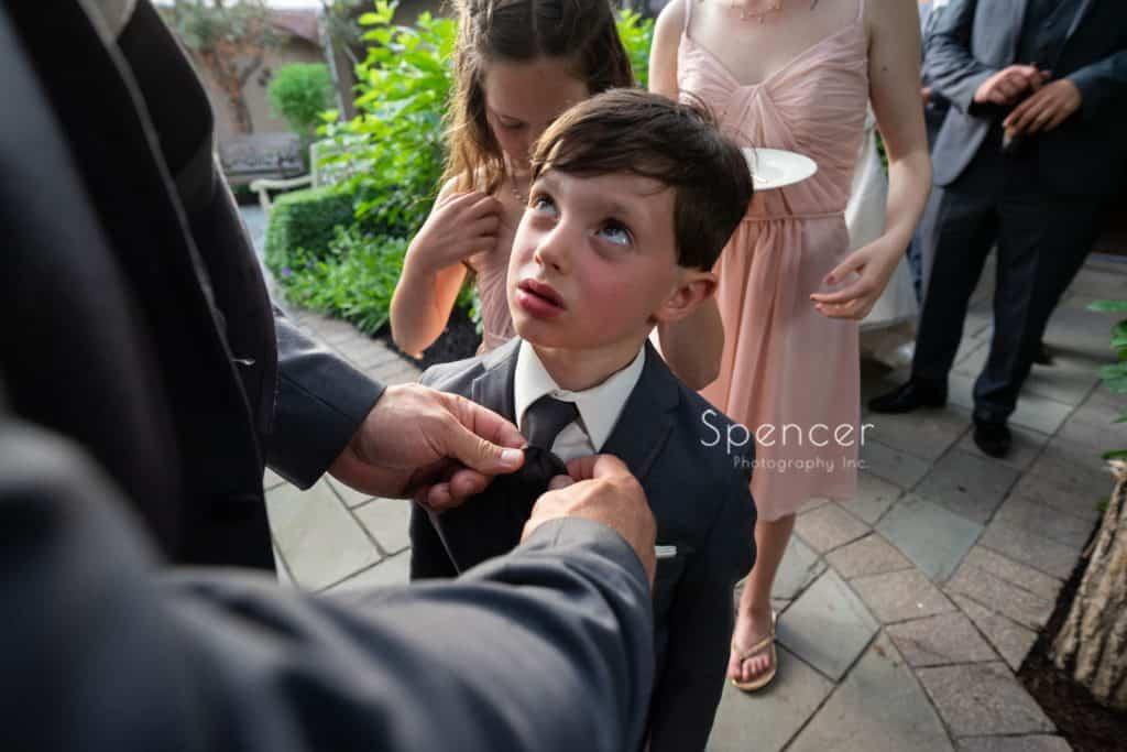 dad straightening ring bearers tie before wedding reception at Thorncreek