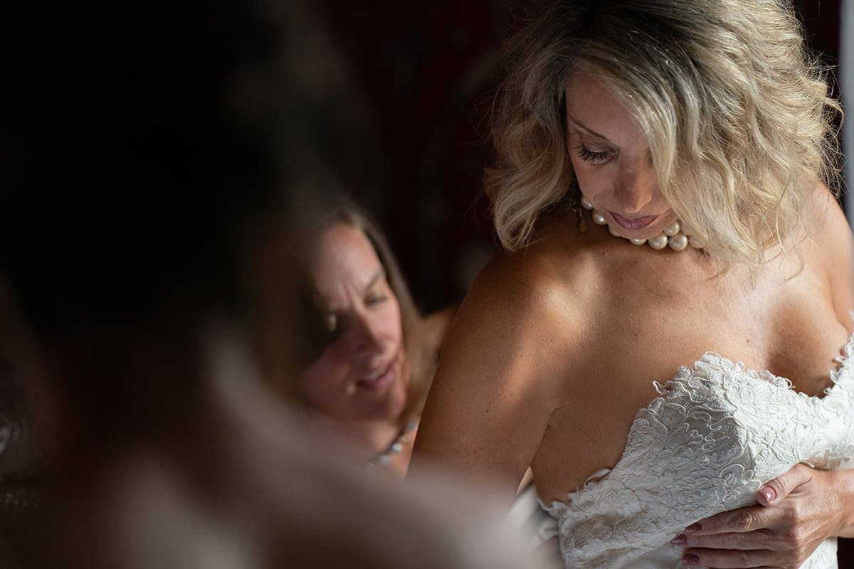 Bride putting on wedding dress at Bertram Inn