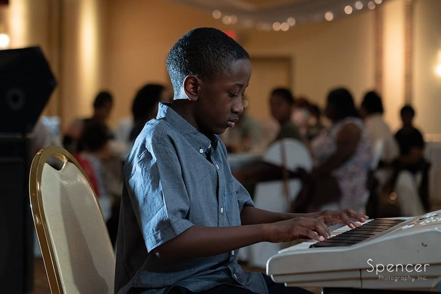 young boy playing piano at surprise birthday party
