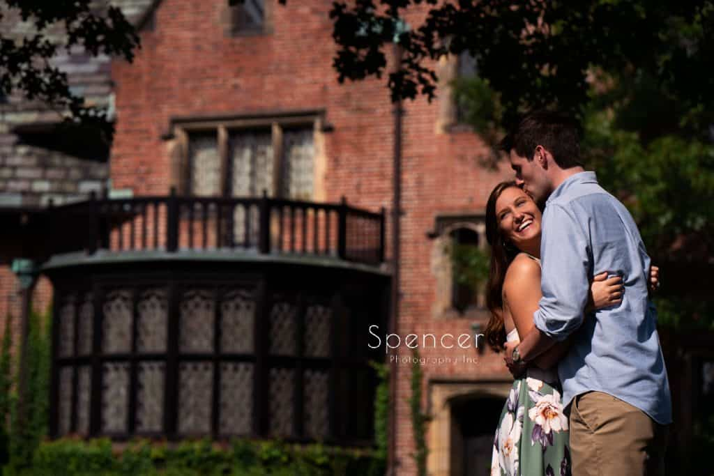 couple embracing during engagement pictures in front of Stan Hywet