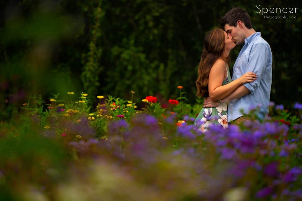 couple kissing in flower garden during engagement pictures at Stan Hywet