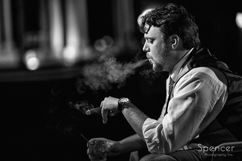 black and white picture of groom smoking cigar