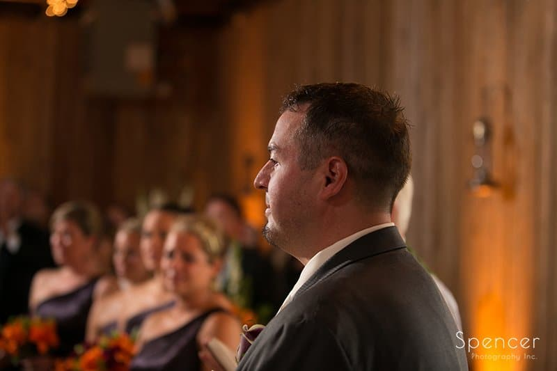 groom watching bride walk aisle at wedding at Brookside Farm
