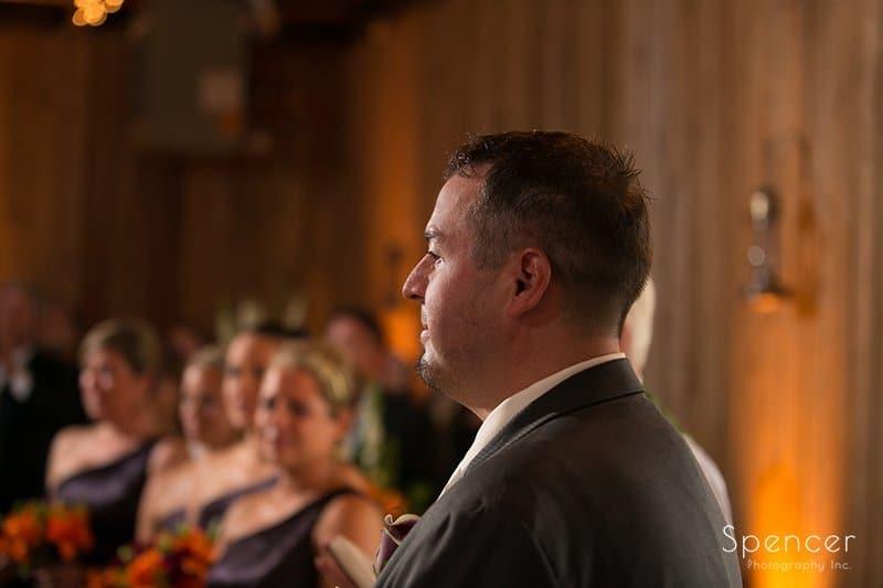 groom watching bride walk aisle at wedding at Brookside Farm