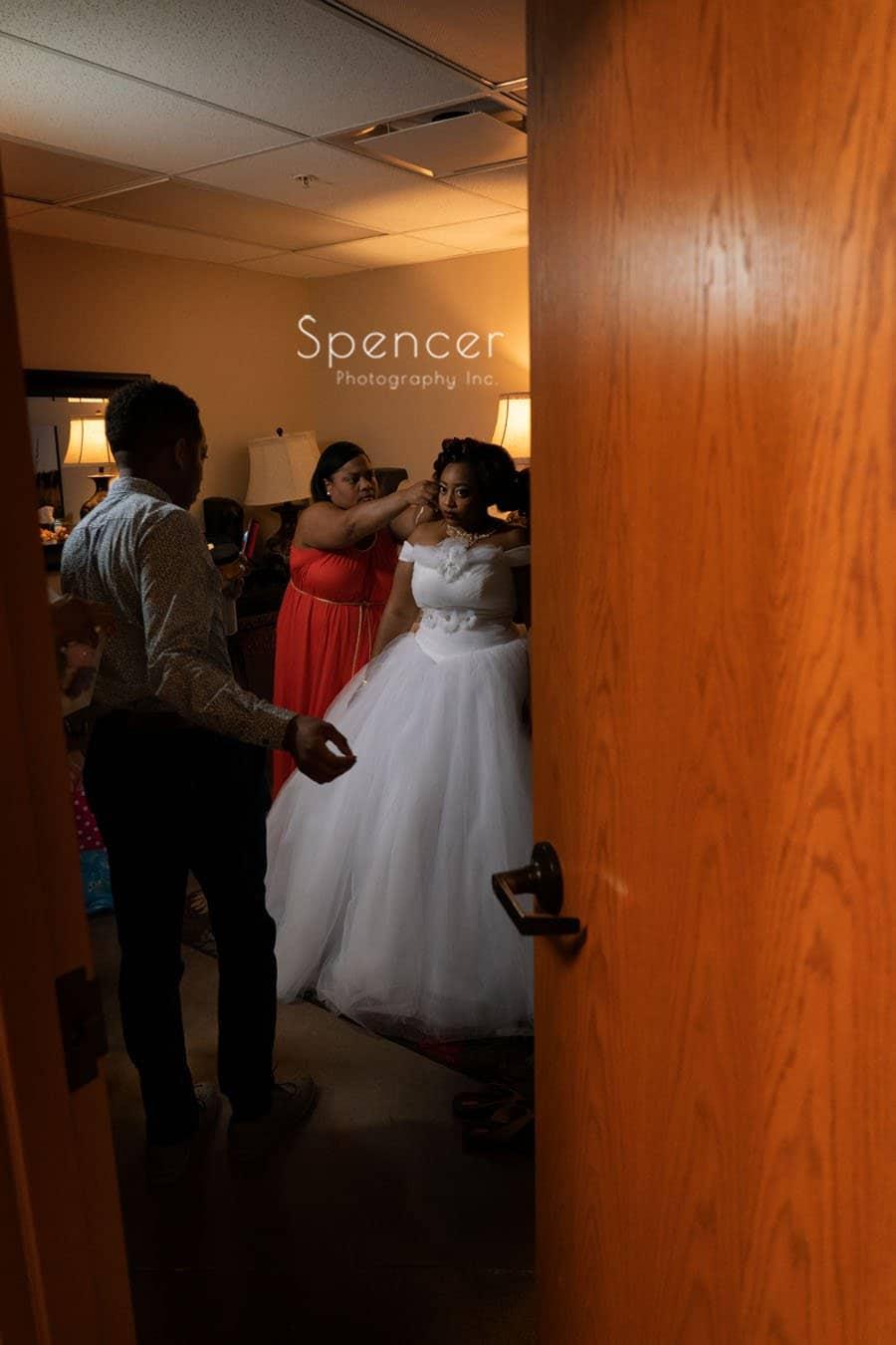 picture thru door of bride putting on wedding dress