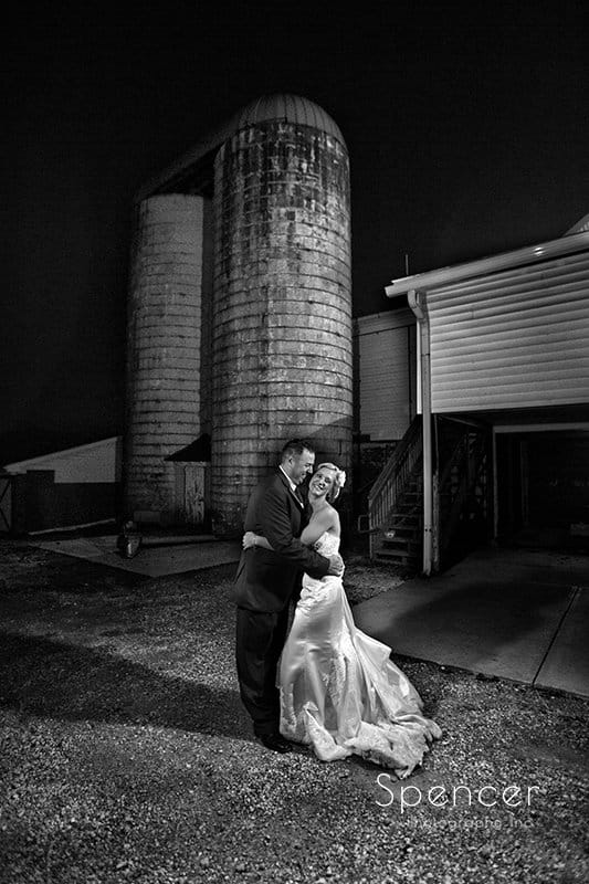 wedding picture of groom hugging bride in front of barn at Brookside Farm