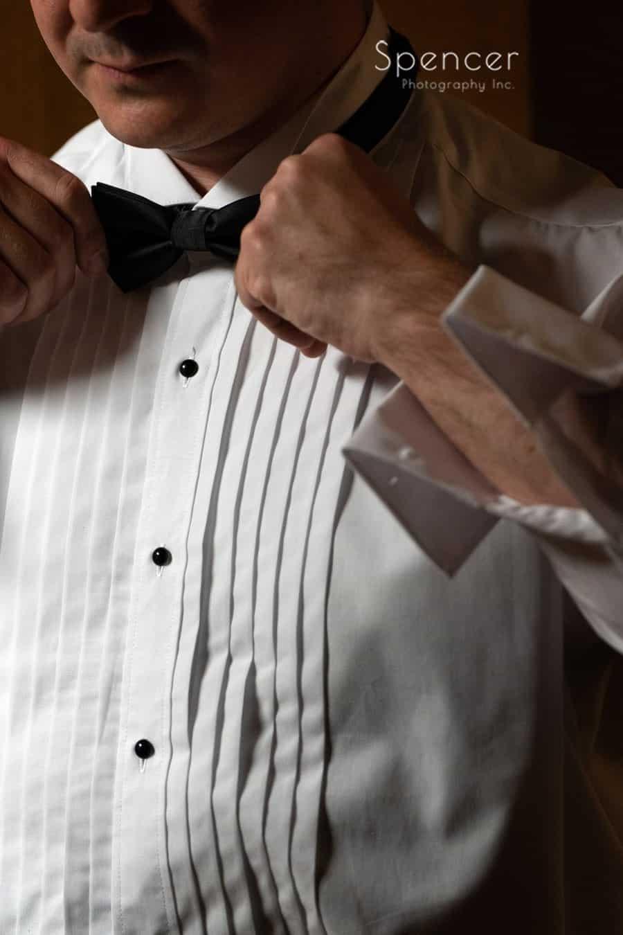 groom adjusting tie at wedding in Oberlin