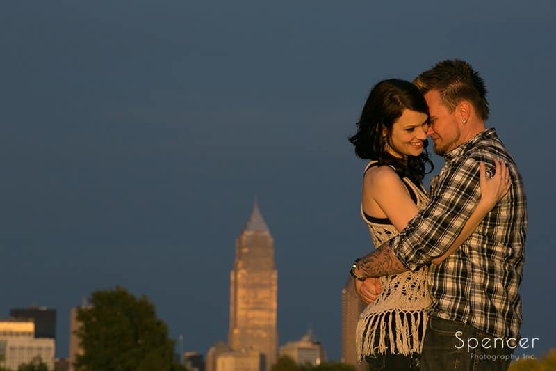 couple hugging in engagement pictures in front of Cleveland skyline
