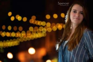 girl smiling in her unique senior pictures in front of café lights