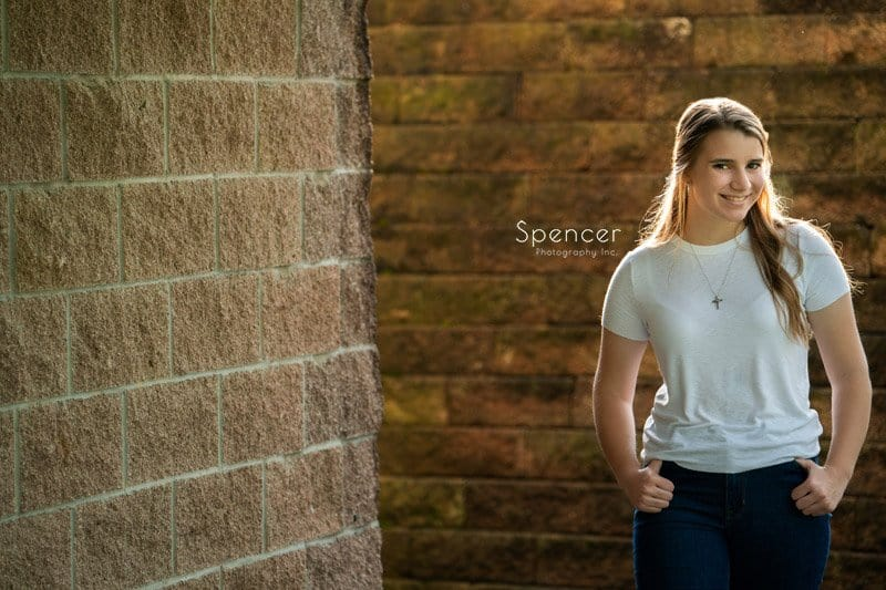 senior picture of girl in white shirt in front of brick wall