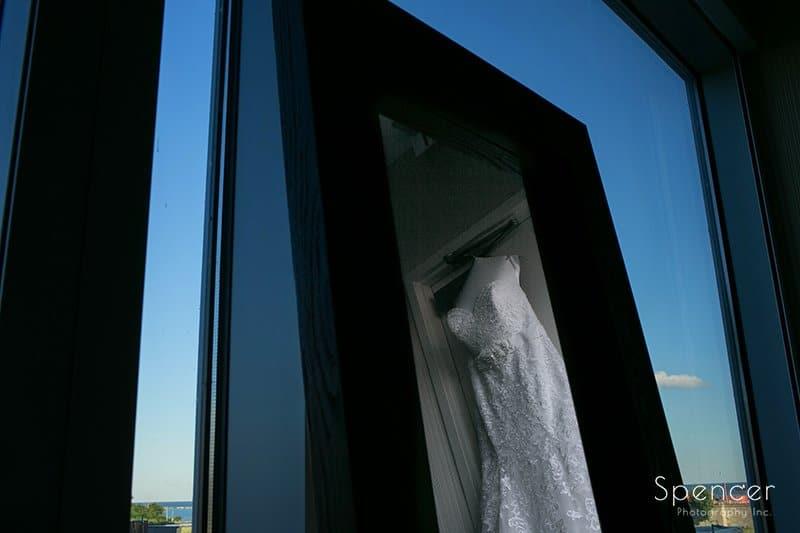 wedding dress hanging in window on wedding day at Aloft Cleveland