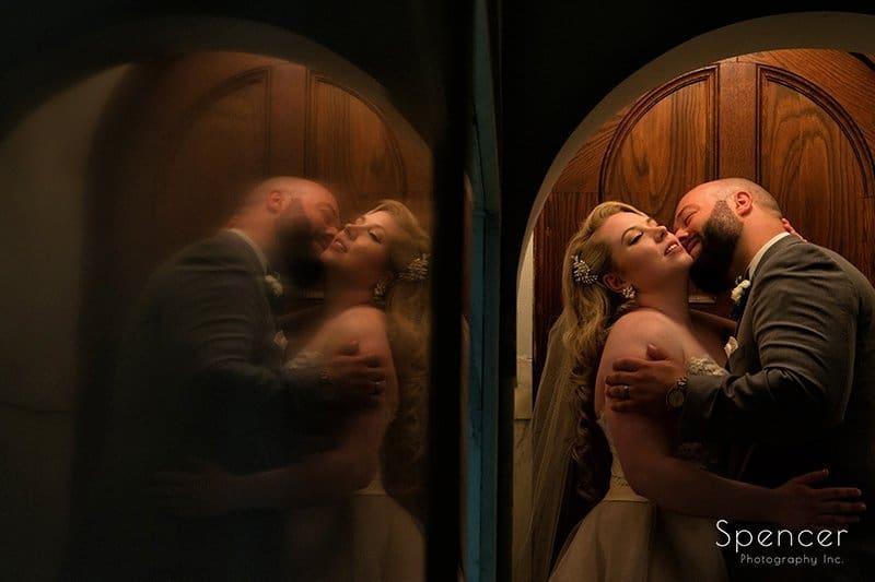 gorgeous wedding picture of groom kissing bride at Communion of Saints Parish