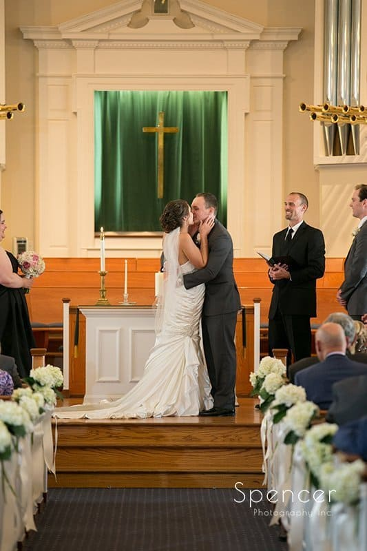 first kiss at wedding ceremony at Church on the Lakes