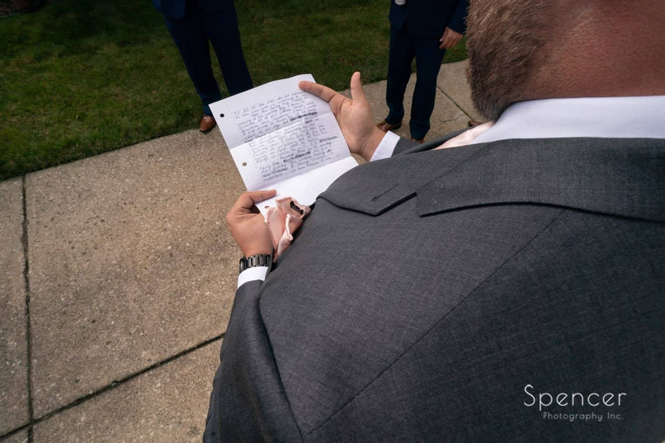 groom reading letter from bride on wedding day