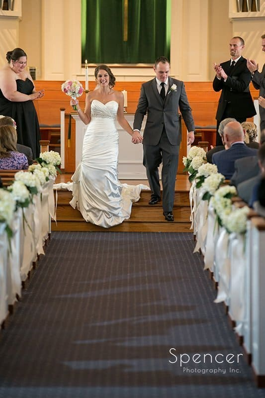 bride and groom walking down the aisle after church on the lakes