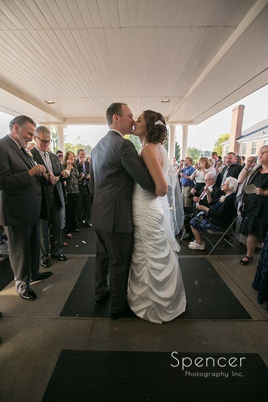bride and groom kiss as they exit wedding ceremony at Church on the Lakes