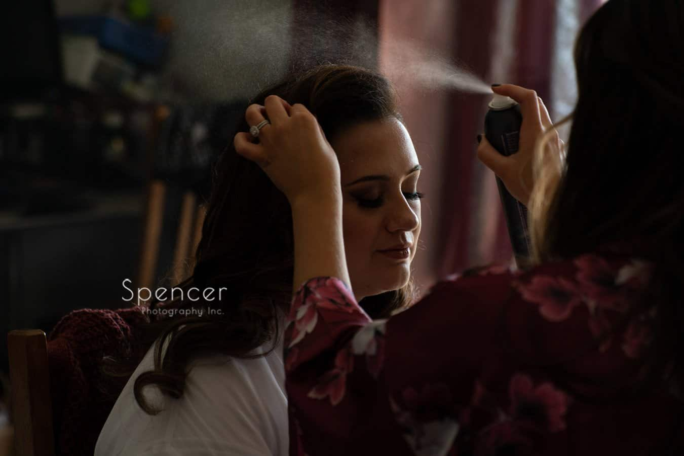 bride getting hair spray before her wedding in Mayfield