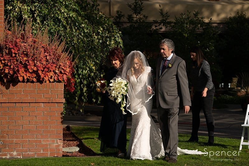 parents walking bride to wedding ceremony at Firestone Country Club