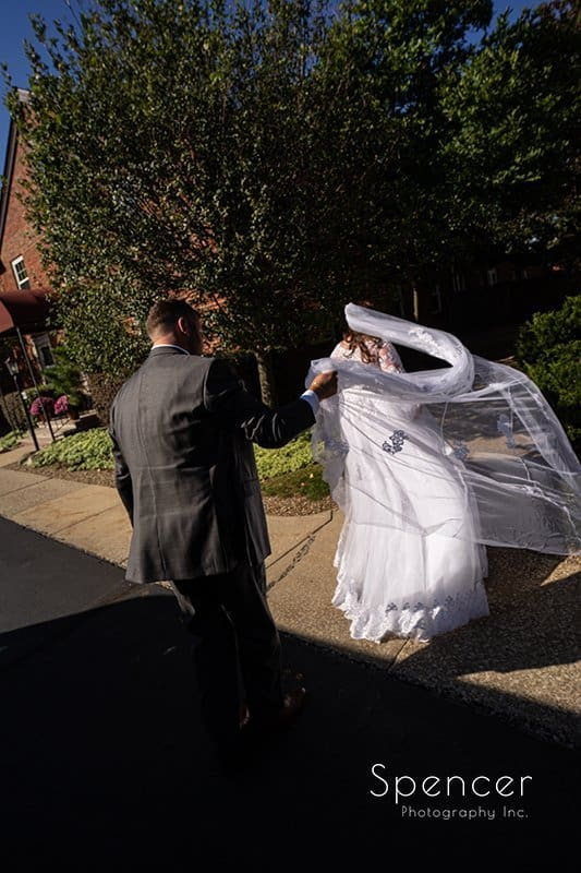groom holding brides veil as it blows in the wind