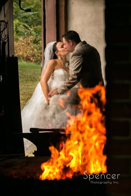 bride and groom kissing in front of fire at Country Cottage and Gardens