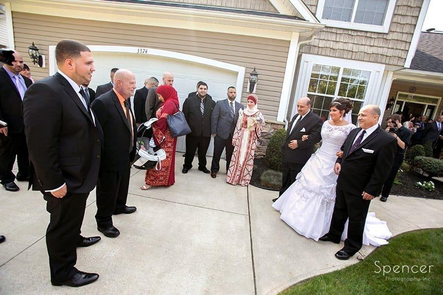 father walks bride to groom during Muslim wedding