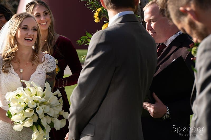 bride smiling at groom at wedding ceremony at Firestone Country Club
