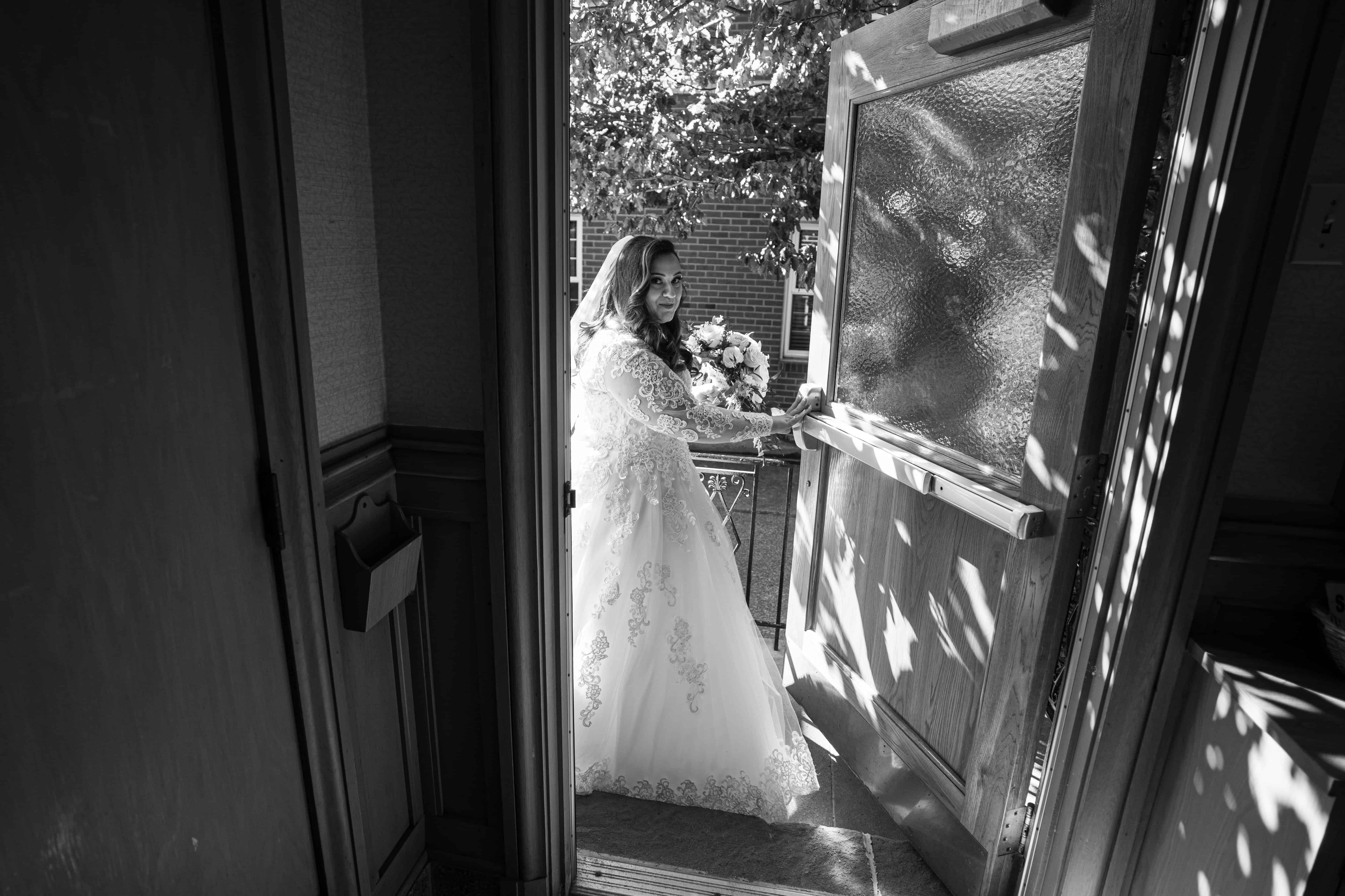 black and white picture of bride entering Church of Saint Clare