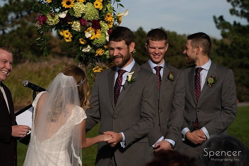 groom smiling at bride at wedding ceremony at Firestone Country Club