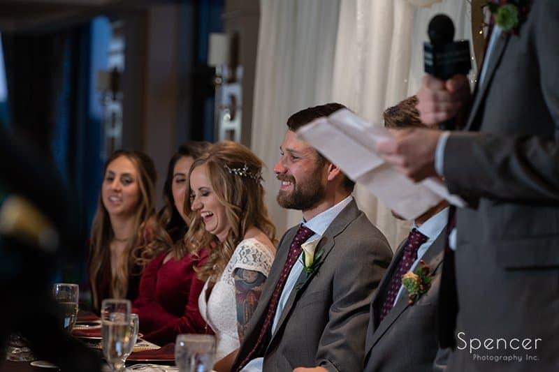 bride and groom laughing at groomsmen speech