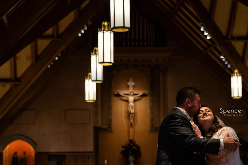 groom kissing bride at st clare church mayfield ohio