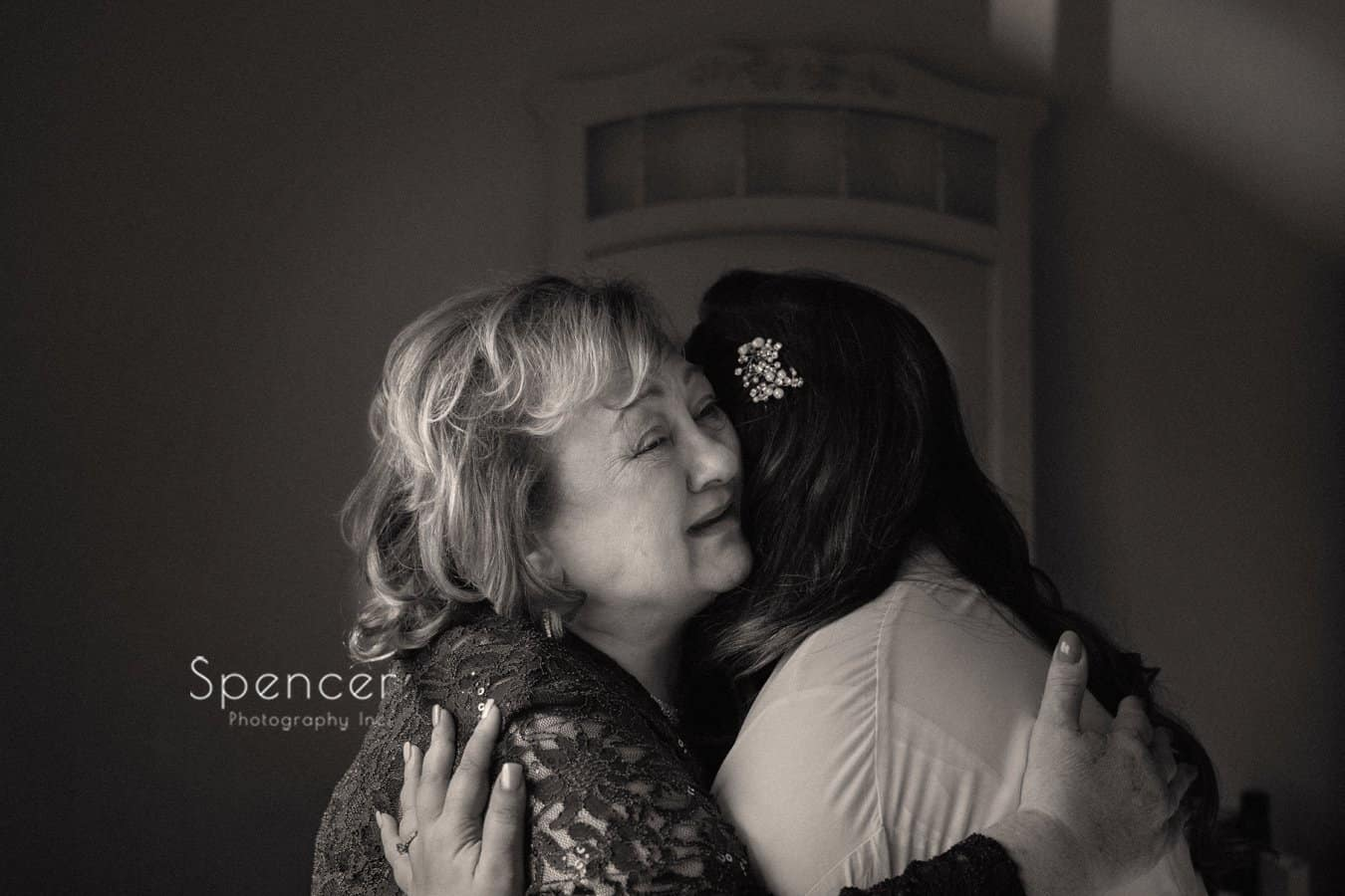 mother crying while hugging her daughter on wedding day