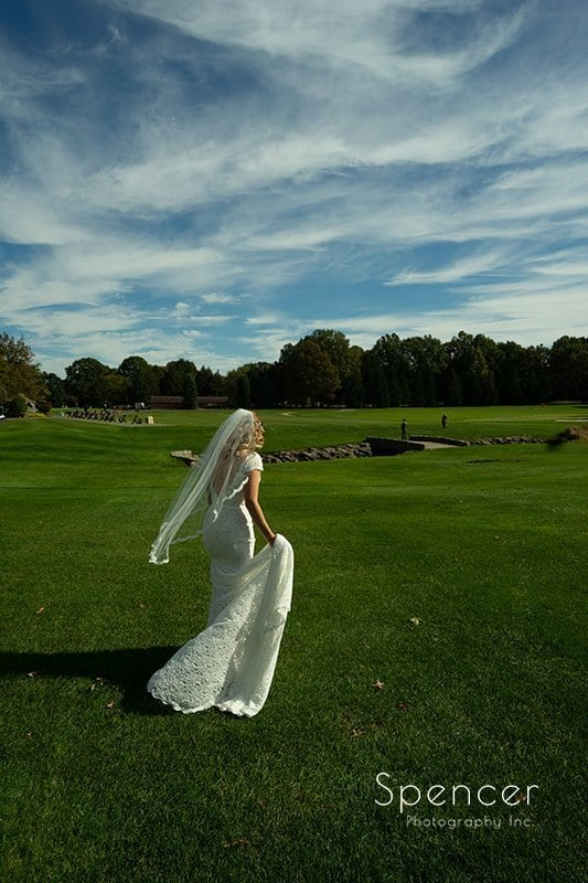 bride walking on golf course at Firstone on her wedding day