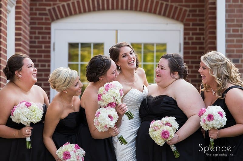 bridesmaids laughing in front of Church on the Lakes Canton