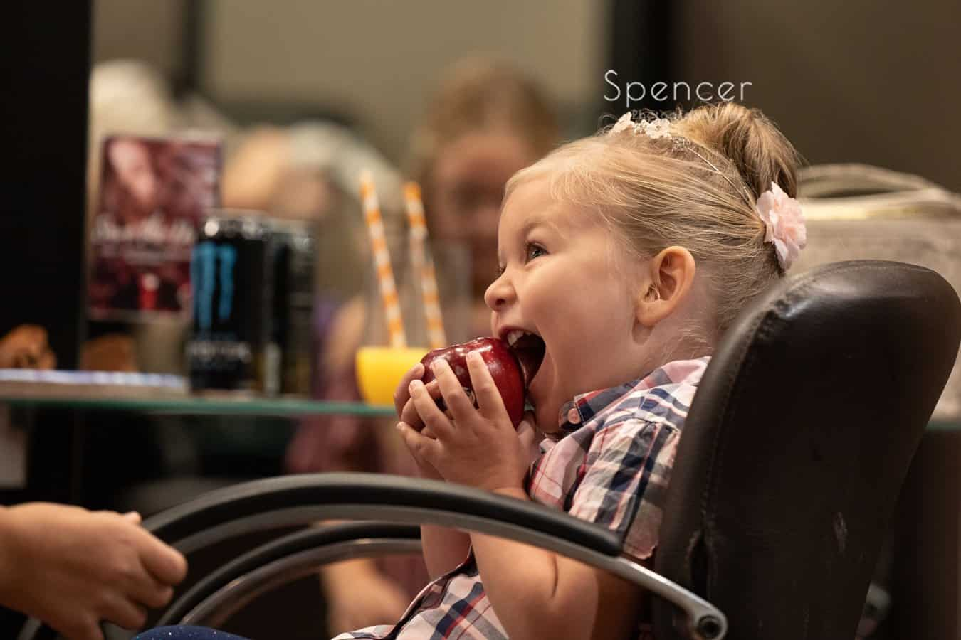 flower girl biting into apple