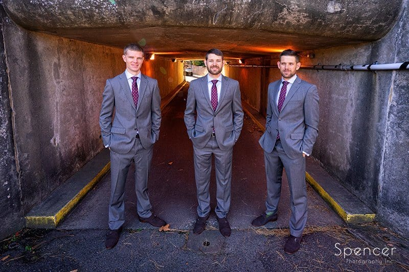 groom standing with groomsmen at tunnel at Firestone Country Club