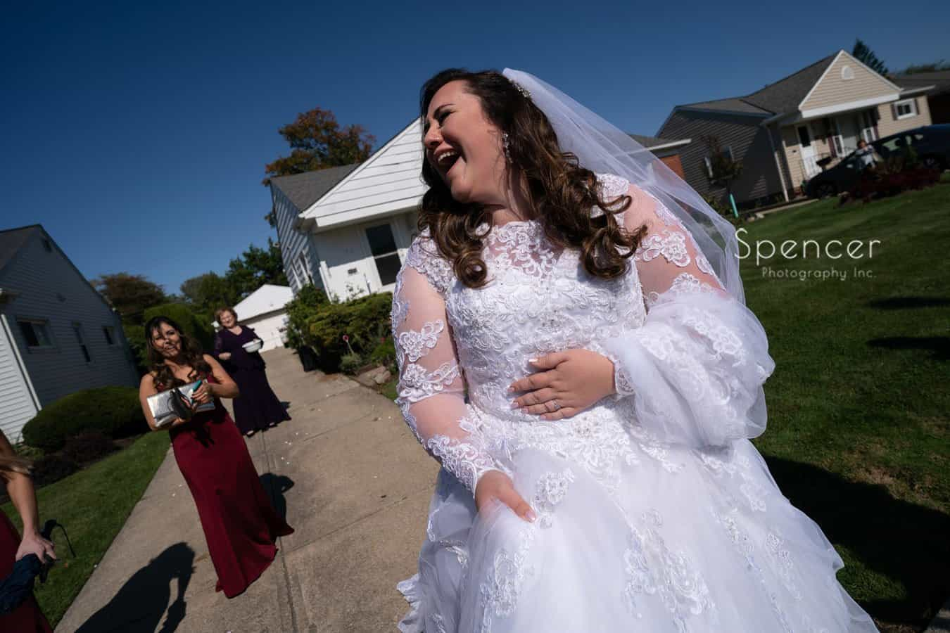 bride laughing at mother house on wedding day