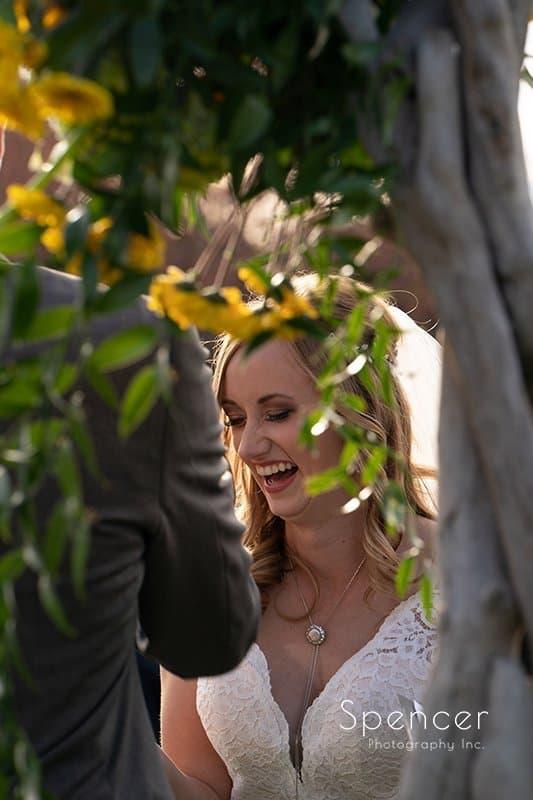 bride smiling thru flowers at Firestone wedding ceremony