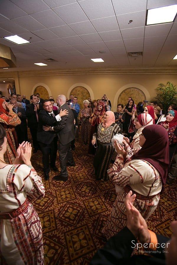 groom hugs wedding guest