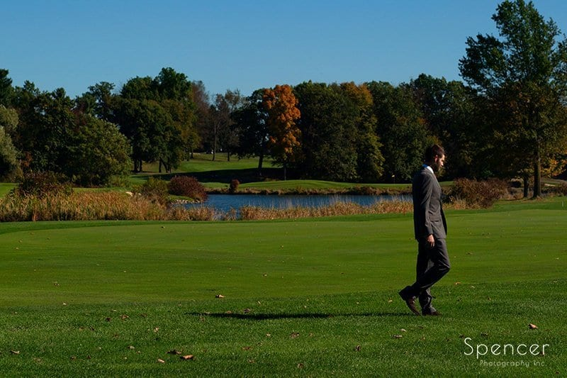groom walking on golf course at Firestone Country Club