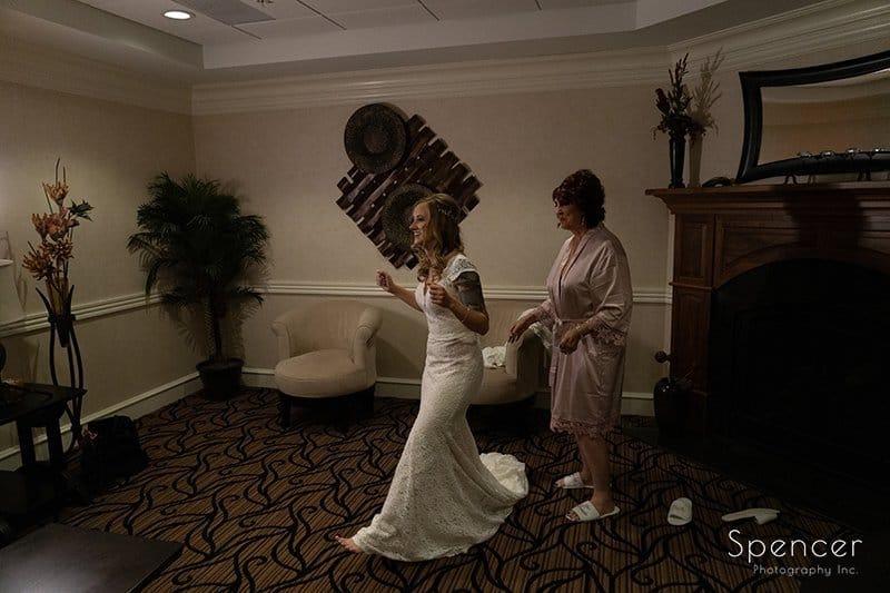 mom helping bride with wedding dress at Firestone Country Club