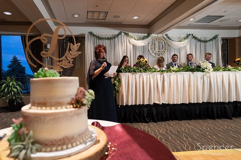 mother of bride speaking with cake in foreground