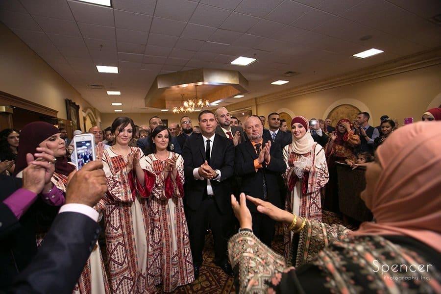 groom being greeted by brides mom at Muslim wedding reception