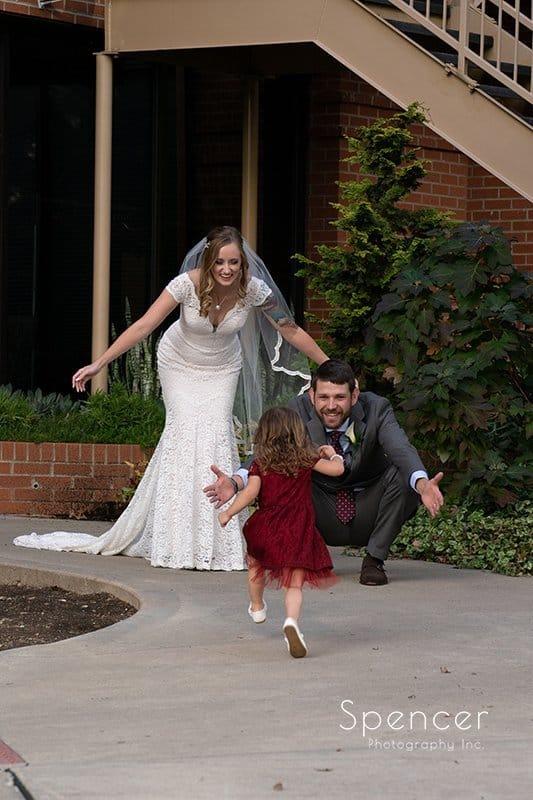 bride and groom hug flower girl at Firestone wedding ceremony