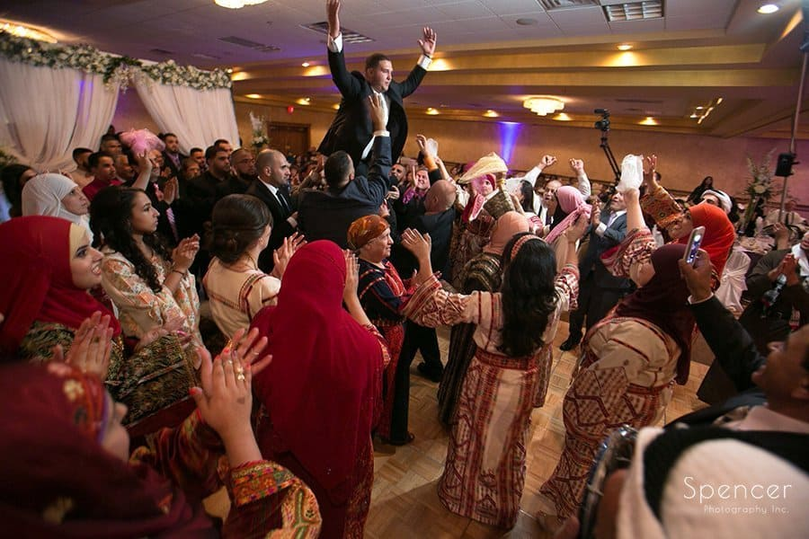 groom being carried into his Muslim wedding reception