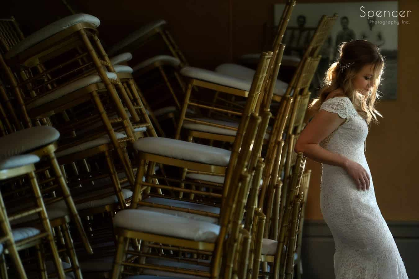wedding picture of bride against chairs at Firestone Country Club