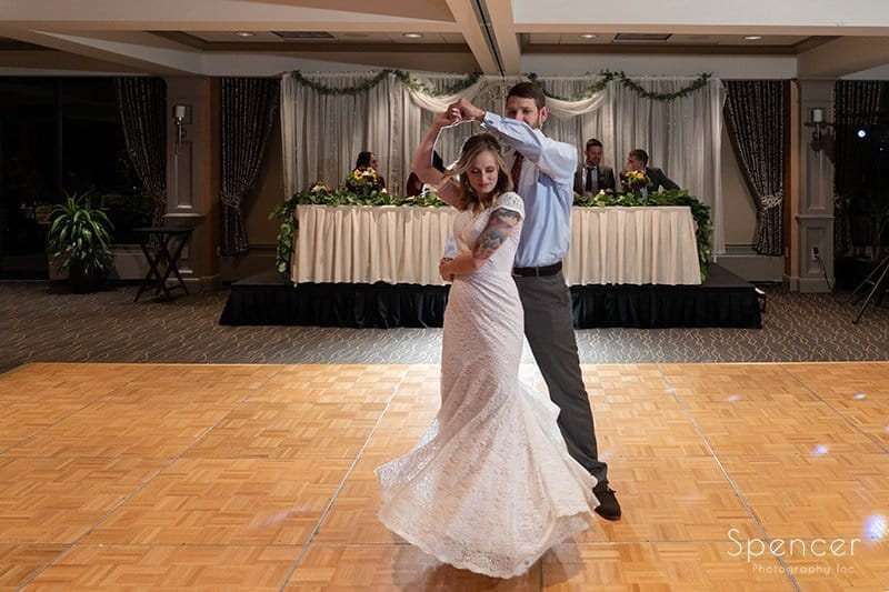 groom spins bride during first dance at Firestone Country Club
