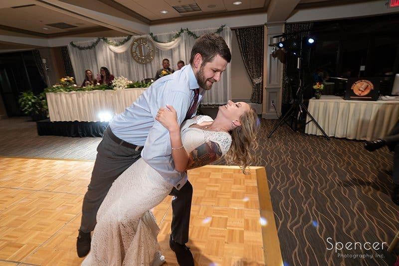 groom dipping bride at wedding reception at Firestone