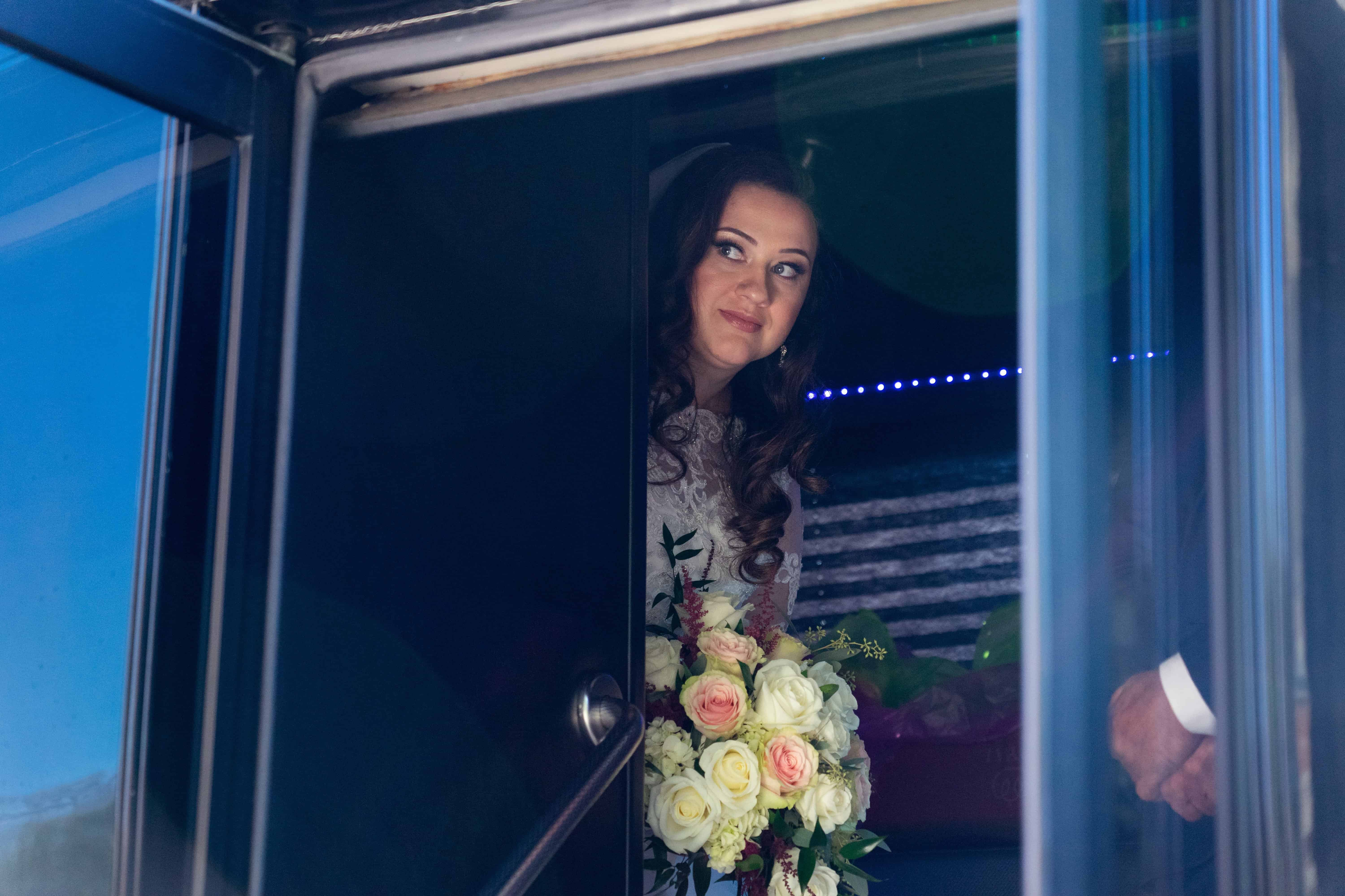 bride peering out of limo before her wedding at st clare church