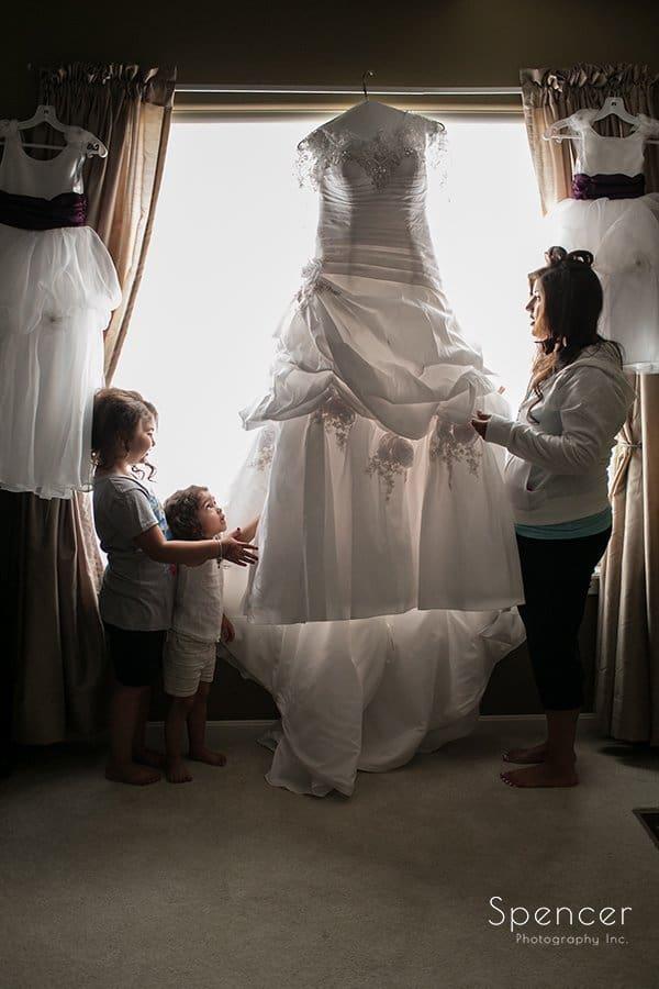 bride with flower girls adjusting wedding dress